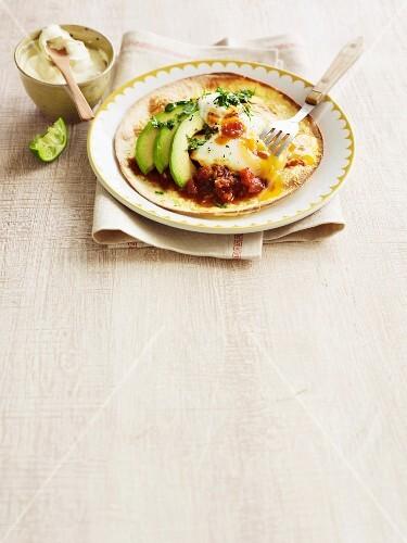 Tortilla with huevos rancheros, avocado, tomato sauce and sour cream (Mexico)