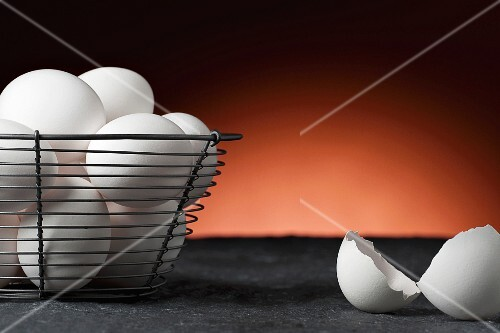 White eggs in a wire basket next to eggshells