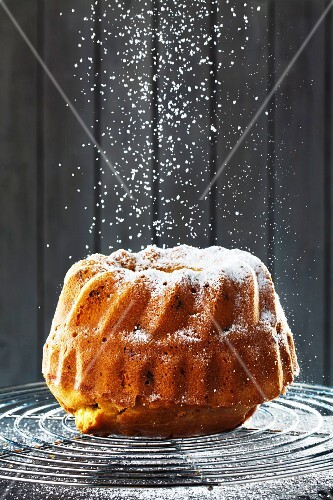 A birthday Bundt cake being dusted with icing sugar