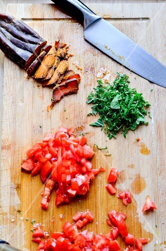 Bottarga, chopped tomatoes and basil with a knife in chopping board