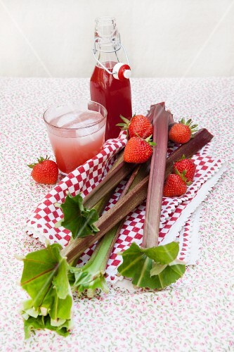 A bottle of rhubarb and strawberry syrup and in a glass with sparkling water as a spritzer