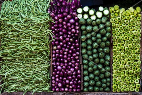 A vegetables stand with beans, aubergines, bitter melons and peppers