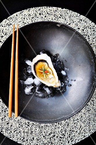 An oyster with ginger, miso and chilli on ice cubes in a black bowl with chopsticks (Japan)
