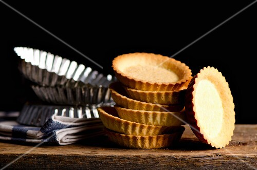 Stack of tartlet bases and tartlet tins on a wooden board