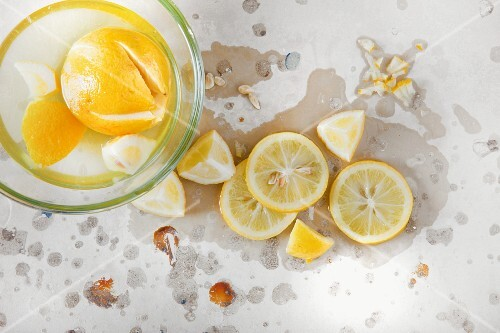 Lemons in brine in a glass bowl and on a stone surface