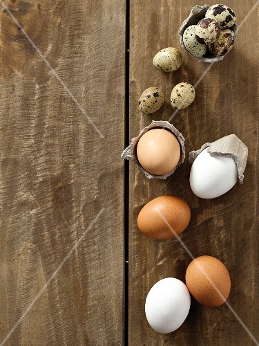 Brown and white chicken eggs and quail's eggs on a wooden surface