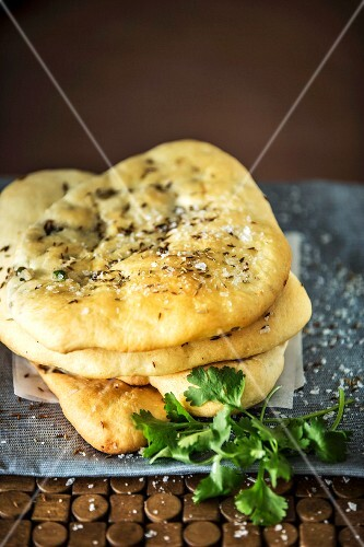 A stack of naan breads with a potato filling and cumin seeds