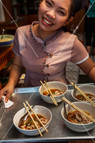 A waitress serving noodle soup (Thailand)