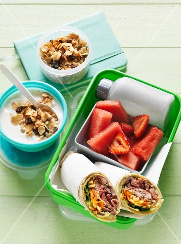 A lunchbox with wraps, fruit and muesli
