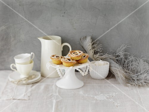 An arrangement of coffee crockery with mince pies on a cake stand