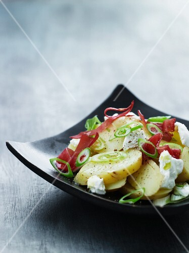 Potato salad with onions, ham and goat's cheese
