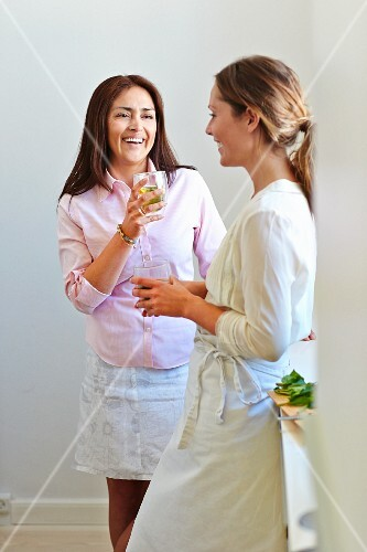 Two woman in a kitchen with aperitifs