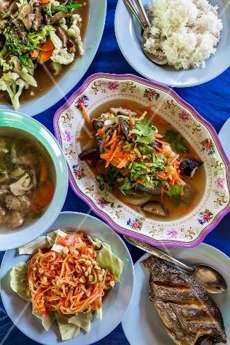 Thai dishes, fish, som tam, papaya salad, vegetables and rice
