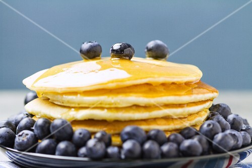 A stack of pancakes with maple syrup and fresh blueberries