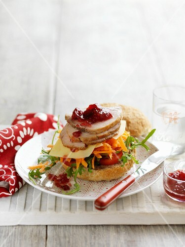 A vegetable, roast pork and cranberry sauce sandwich