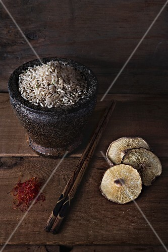 An arrangement of rice, shiitake mushrooms, saffron and chopsticks