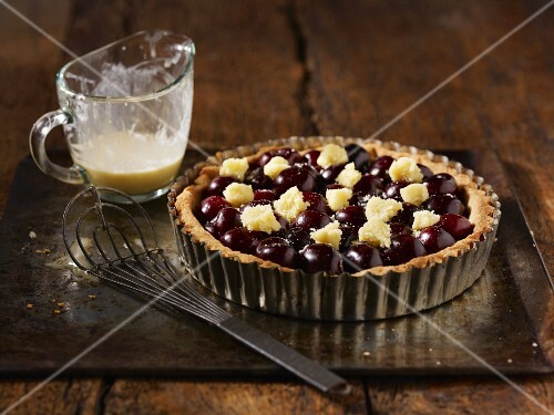 Black cherry tart with frangipane in a tart in on a baking tray