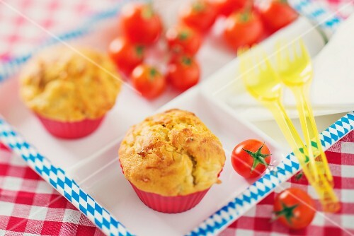 Muffins with bratwurst and sauerkraut on a tray with tomatoes and plastic forks