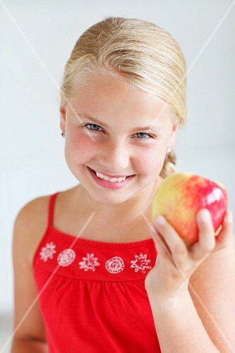 A smiling blond girl holding an apple