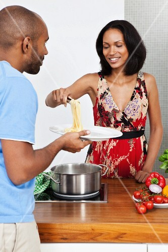 A young woman serving spaghetti to a young man
