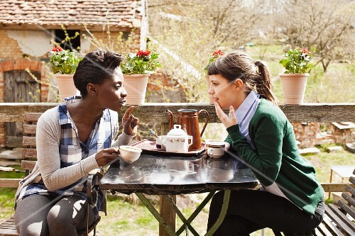 Two women having coffee and a chat in a garden