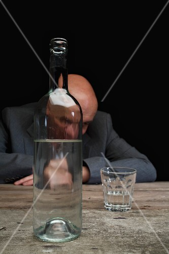 A depressed businessman with a bottle of schnapps and a half empty glass