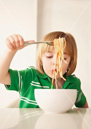 Boy eating spaghetti with tomato sauce