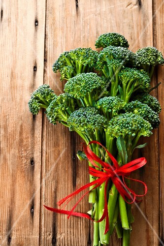 Broccolini with a red ribbon on a wooden surface