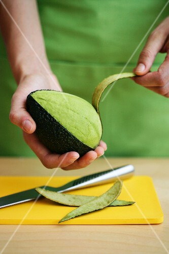 A avocado being peeled