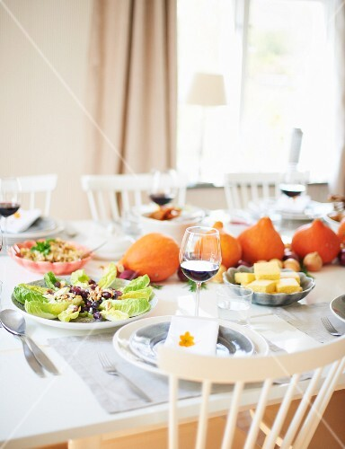 A table laden with salad and decorative pumpkins in a dining room