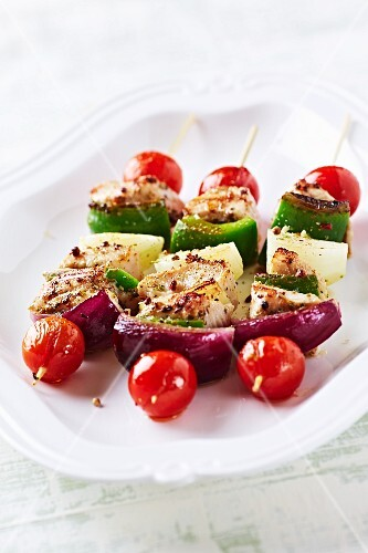 A plate of chicken and vegetable skewers