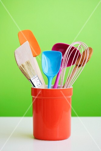 Colourful kitchen utensils in an orange ceramic pot