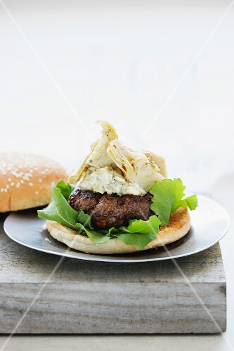 A hamburger with artichokes