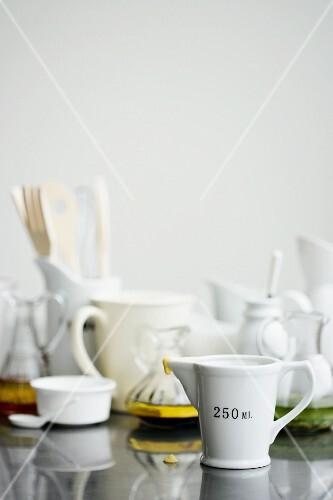 A measuring jug, kitchen utensils, jugs and salad dressings