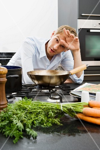 A tired adult man at the stove in a kitchen