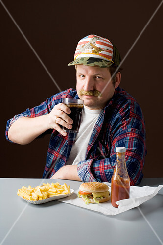 A stereotypical American man with a burger, fries and a cola