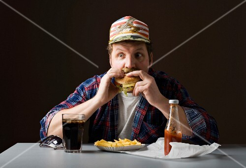 A stereotypical American man eating burger and fries