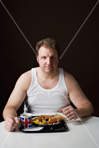 A stereotypical Englishman eating breakfast