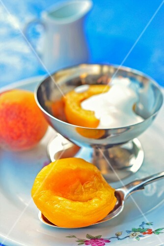 Peaches with cream in a silver dish