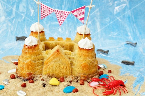 A sandcastle cake with beach decorations