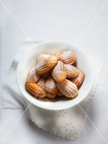 A bowl of madeleines with icing sugar