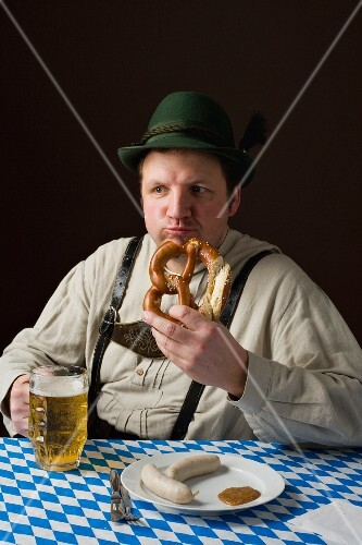 A stereotypical German man wearing lederhosen eating a pretzel and white sausage with a beer