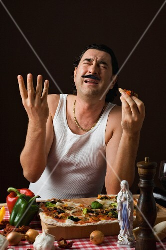 A stereotypical Italian man eating pizza and gesturing with his hands