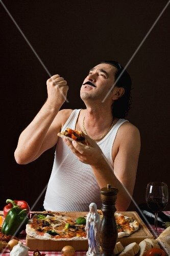 A stereotypical Italian man gesticulating while eating pizza