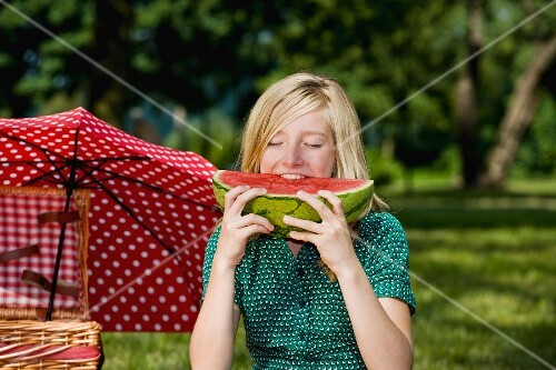 A girl eating a slice of watermelon at a picnic