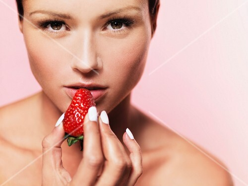 A woman holding a strawberry up to her mouth