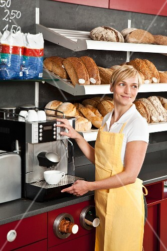 A sales assistant using an espresso machine in a bakery
