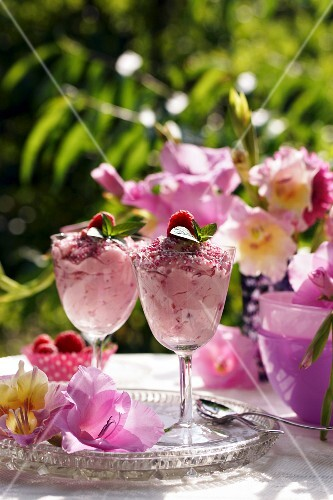 Raspberry mousse and gladioli flowers on a summery garden table