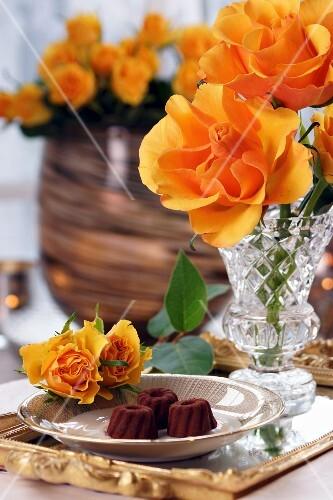 Chocolate pralines and orange coloured roses