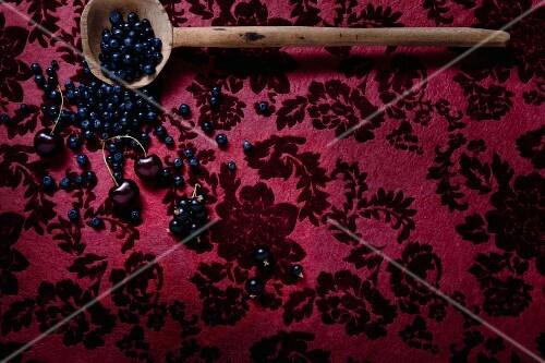 Berries and fruit on dark red velvet